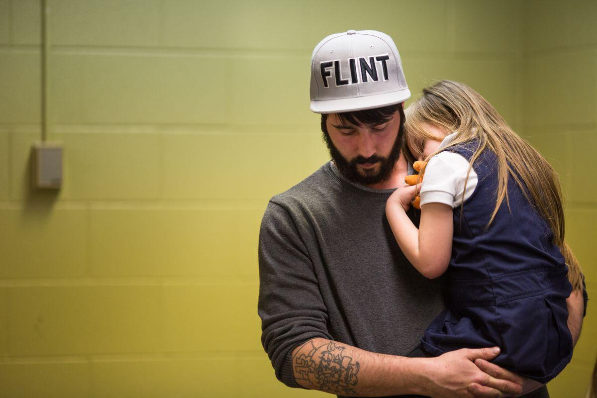 Flint water crisis. Man holding young girl.